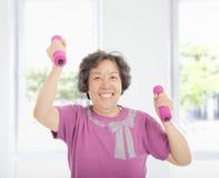 Счастливая старшая женщина разрабатывая с гантелями Стоковые Изображения RF