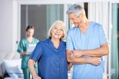Счастливая старшая женщина стоя с мужским смотрителем стоковая фотография rf