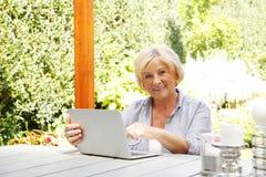 Счастливая старшая женщина с компьтер-книжкой Стоковое Фото