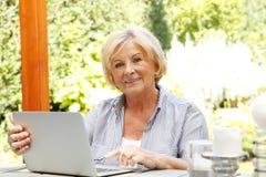 Счастливая старшая женщина с компьтер-книжкой Стоковое Изображение RF
