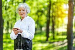 Счастливая старшая красивая женщина имея период отдыха во время тренировки снаружи Стоковые Фотографии RF