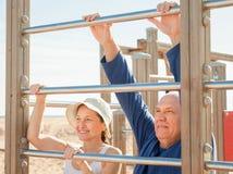Счастливая старшая тренировка пар на баре тяги-вверх Стоковая Фотография