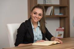 Счастливая студентка в библиотеке с книгой Стоковые Изображения