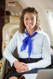 Счастливая стюардесса сидя при закрытых дверях двигатель Стоковые Изображения