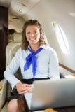 Счастливая стюардесса с двигателем компьтер-книжки при закрытых дверях Стоковые Фотографии RF