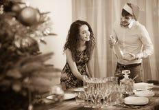 Счастливая таблица рождества сервировки человека и девушки для гостей Стоковые Фото