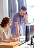Счастливая творческая команда вызывая на телефоне в офисе Стоковые Фотографии RF