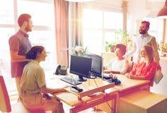 Счастливая творческая команда говоря в офисе Стоковое фото RF