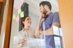 Счастливая творческая команда говоря на офисе Стоковое фото RF