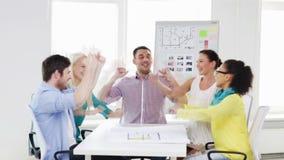 Счастливая творческая команда празднуя победу в офисе видеоматериал