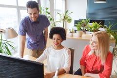 Счастливая творческая команда с компьютером в офисе Стоковые Изображения
