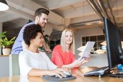 Счастливая творческая команда с компьютером в офисе Стоковое Изображение