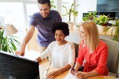 Счастливая творческая команда с компьютером в офисе Стоковая Фотография