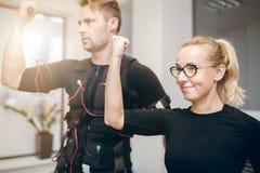 Счастливая тренировка женщины на спортзале с спортсменом Стоковая Фотография RF