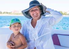 Счастливая усмехаясь бабушка и внук имея потеху тратя время совместно на пляже Маленький ребёнок семья счастливая Положительный ч Стоковое фото RF