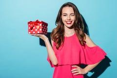 Счастливая усмехаясь девушка в платье держа присутствующую коробку и подмигивать Стоковые Изображения
