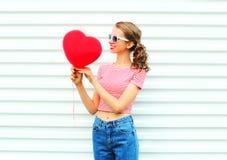 Счастливая усмехаясь девушка смотря на форме сердца воздушного шара над белизной Стоковая Фотография RF