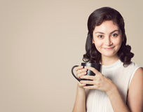 Счастливая усмехаясь женщина в вскользь одеждах держа белую чашку coffe Стоковая Фотография