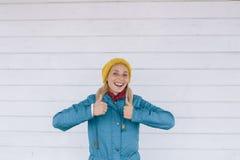 Счастливая усмехаясь женщина в желтом цвете связала шляпу и синий пиджак показывая большие пальцы руки вверх Стоковое Изображение RF