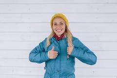 Счастливая усмехаясь женщина в желтом цвете связала шляпу и синий пиджак показывая большие пальцы руки вверх Стоковое фото RF