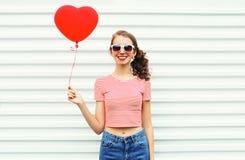 Счастливая усмехаясь женщина держа в форме сердца воздушного шара руки над белизной Стоковая Фотография