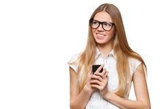 Счастливая усмехаясь женщина держа мобильный телефон смотря прочь изолированный на белизне Стоковое Фото