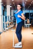 Счастливая усмехаясь женщина на масштабах на спортзале стоковая фотография