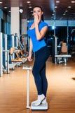 Счастливая усмехаясь женщина на масштабах на спортзале стоковые изображения