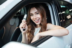 Счастливая усмехаясь женщина сидя внутри ее нового автомобиля стоковое фото rf