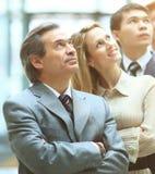 Счастливая усмехаясь команда дела стоя в ряд в офисе и смотря до виртуальная реклама Стоковые Изображения