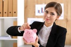 Счастливая усмехаясь красивая коммерсантка кладя деньги штыря в штырь Стоковое фото RF