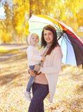 Счастливая усмехаясь мать и ребенок с зонтиком идя в осень стоковые изображения
