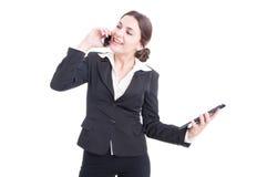 Счастливая усмехаясь молодая бизнес-леди используя таблетку и телефон Стоковые Фото