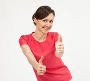 Счастливая усмехаясь молодая женщина показывая большие пальцы руки поднимает знак стоковое фото