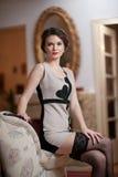 Счастливая усмехаясь привлекательная женщина нося элегантное платье и черные чулки сидя на софе подготовляют Красивая молодая чув Стоковая Фотография RF
