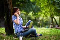 Счастливая усмехаясь работа девушки онлайн Стоковое Фото