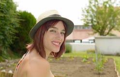 Счастливая усмехаясь соломенная шляпа девушки нося в саде Стоковое Фото