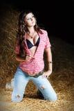 Счастливая усмехаясь тонкая женщина девушки при лоснистое вьющиеся волосы сидя на сене на ферме в джинсах и striped жилете. Стоковая Фотография