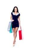 Счастливая усмехаясь хозяйственная сумка владением женщины Женщина изолированная над белой предпосылкой Стоковое фото RF