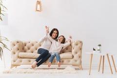 Счастливая услаженная девушка сидя с ее матерью Стоковое Изображение
