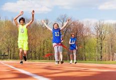 Счастливая финишная черта скрещивания девочка-подростка в гонке Стоковые Фото
