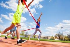 Счастливая финишная черта скрещивания девушки на беговой дорожке Стоковое Изображение RF