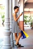Счастливая чернокожая женщина песни держа мобильный телефон и хозяйственные сумки Стоковые Фотографии RF
