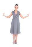 Счастливая шикарная женщина в первоклассном платье указывая перста вверх Стоковые Фото