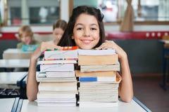 Счастливая школьница отдыхая Chin на штабелированных книгах на Стоковое фото RF