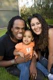 Счастливая biracial семья усмехаясь на парке стоковые изображения