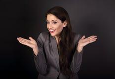 Счастливая confused бизнес-леди показывать руки в сером костюме o Стоковые Фото