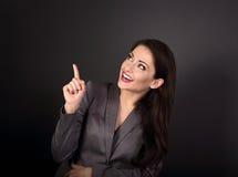 Счастливая excited бизнес-леди в сером костюме показывая и указывая t Стоковое Фото