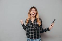 Счастливая excited девушка держа мобильный телефон и празднуя выигрыш