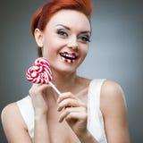 Счастливая red-haired конфета удерживания девушки стоковое изображение